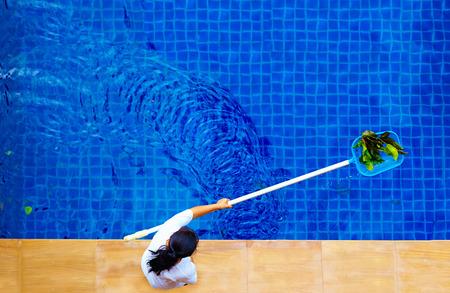 vrouw personeel het zwembad schoonmaken van bladeren