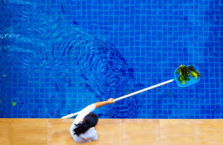 fallen leaves: woman personnel cleaning the pool from leaves Stock Photo