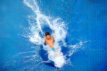 diving pool: man jumping in pool huge splash top view
