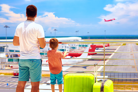 father and son ready for summer vacation while waiting for boarding in international airport