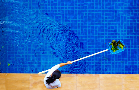 woman personnel cleaning the pool from leaves 스톡 콘텐츠