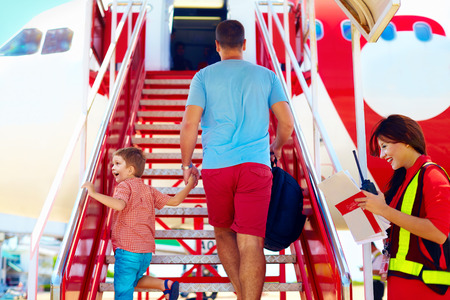 family are boarding on airplane female steward welcomes passengers Stock Photo