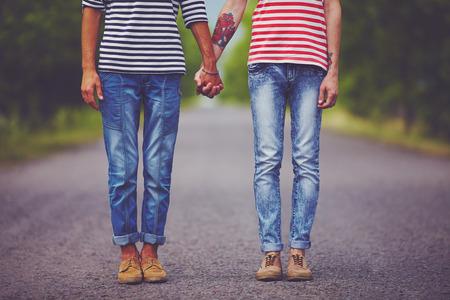 sexo pareja joven: pareja de jóvenes tomados de sexo masculino manos de pie en su camino juntos