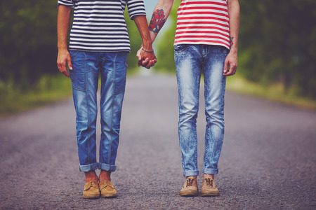 same sex: young male couple holding hands standing on their way together