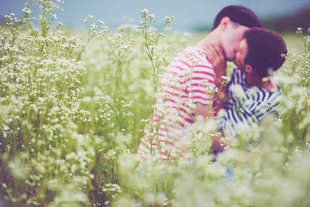 sex tenderness: Defocused male couple kissing in daisy flowers on summer field Stock Photo