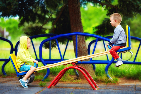 niños en area de juegos: niños lindos que se divierten en el balancín en el patio Foto de archivo