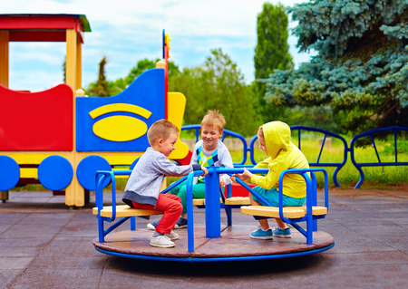 three little friends kids having fun on roundabout at playground