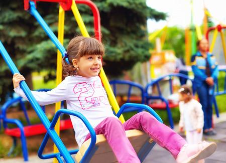 niños en area de juegos: niño lindo niña feliz se divierten en los columpios en el patio