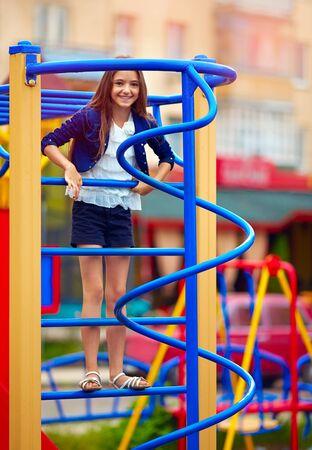 stile: happy kid girl climbs on the stile at playground Stock Photo