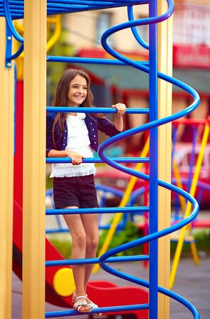 stile: happy kid girl climbs on the stile at playground Stock Photo