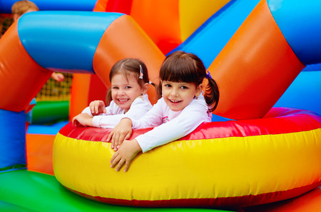happy kids girls having fun on inflatable attraction playground 스톡 콘텐츠
