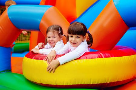 gelukkig kinderen meisjes met plezier op opblaasbare attractie speelplaats Stockfoto