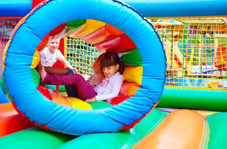 atracci�n: ni�os felices divertirse en la atracci�n inflable parque infantil Foto de archivo