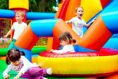 castillos: niños felices divertirse en la atracción inflable parque infantil Foto de archivo