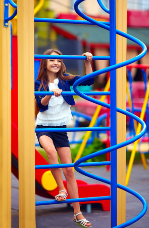 stile: pretty kid girl climbs on the stile at playground