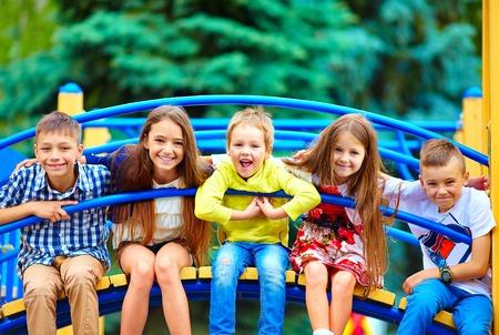 terreno: gruppo di bambini felici divertirsi nel parco giochi Archivio Fotografico