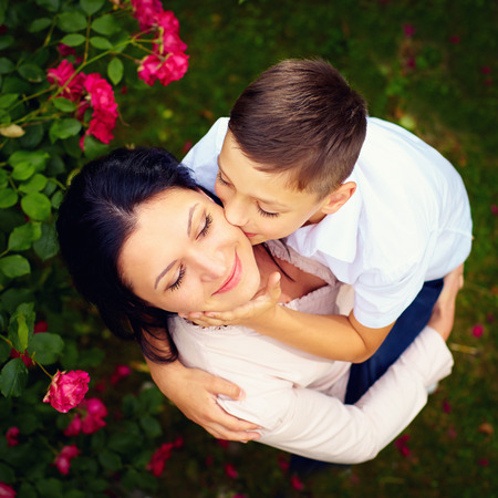 mom son: portrait of happy son kisses mother in spring garden, top view
