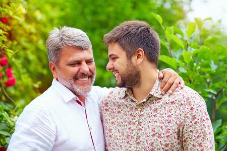 padre e hijo: retrato de feliz padre e hijo hablando al aire libre. De tal palo tal astilla Foto de archivo