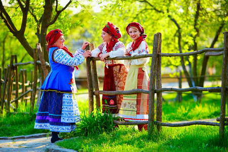 happy ukrainian women dressed in traditional costumes talking on the street