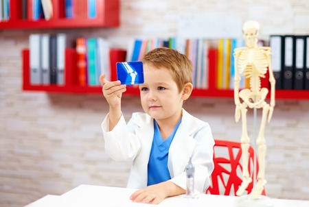 cute kid playing a doctor, looking at x-ray image of leg Banque d'images