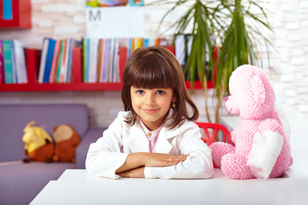play room: beautiful little girl pretending she is a doctor in hospital