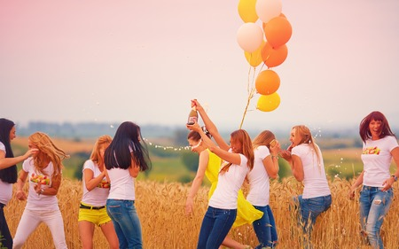 personas saltando: grupo de mujeres felices con la botella de champán en el campo de verano