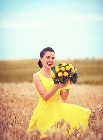 campo de flores: feliz chica baila en campo de trigo de verano, con el ramo de melocotones talla