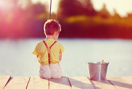 mignon petit garçon sur la pêche de l'étang au coucher du soleil Banque d'images