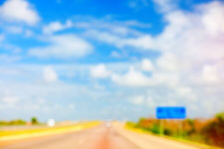 summer sign: defocused background of summer road with traffic sign