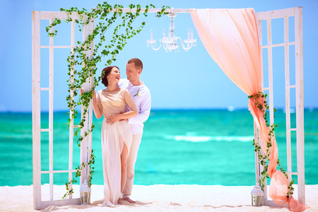 happy wedding couple on decorated tropical beach