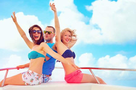 vacation: group of happy friends having fun on yacht, during summer vacation