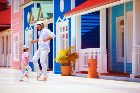 dominican: happy father and son enjoy life, dancing on caribbean street