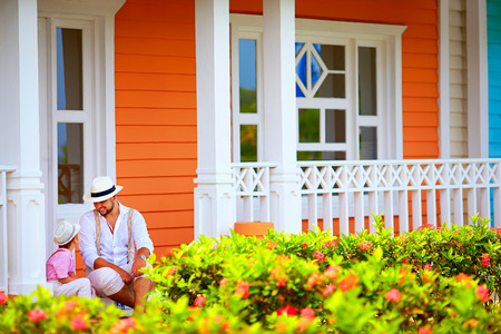 republic: cute father and son sitting and talking on porch, caribbean street