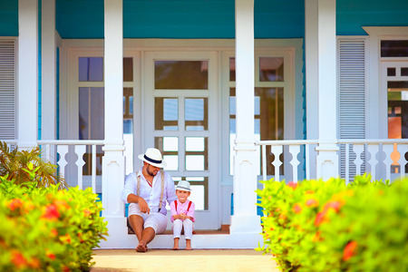 dominican republic: cute father and son sitting on porch, caribbean exterior Stock Photo
