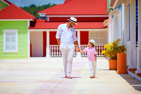 family outside: happy father and son walking on caribbean village street