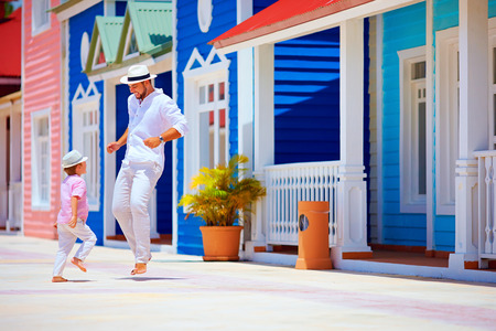 happy father and son enjoy life, dancing on caribbean village street 스톡 콘텐츠