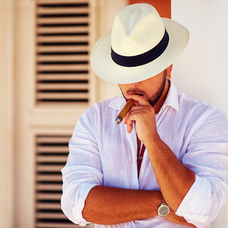 man style: confident handsome man smoking cigar, while leaning on the wall