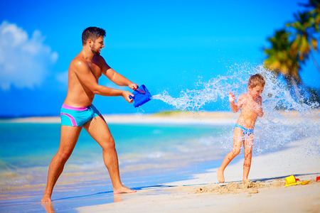 happy father splashing water on laughing son, summer holidays
