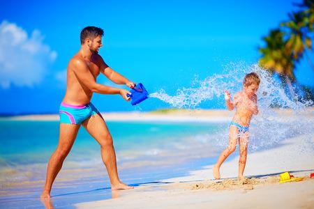在笑的儿子,暑假的愉快的父亲飞溅水