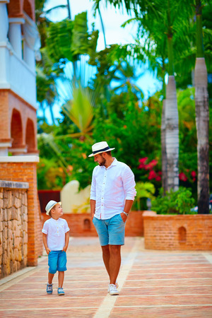 dominican republic: father and son walking on cute tropical street