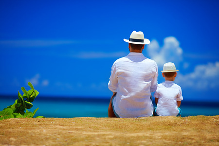 rear view of father and son sitting together on sky horizon Stock Photo