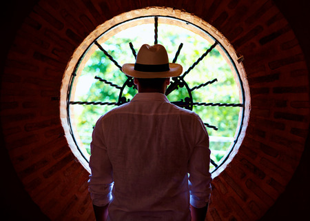 round window: young adult man standing in front of round window in dark room Stock Photo