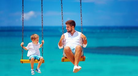 happy family: joyful father and son having fun on swings, sea background