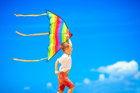 kids wear: happy young boy running with kite on sky background