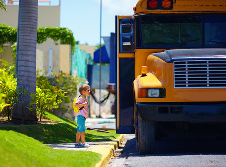 young boy, kid getting on the schoolbus, ready to go to school Foto de archivo