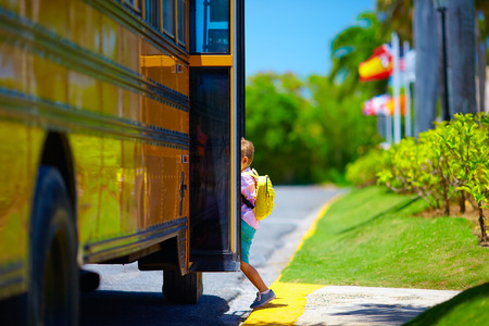go to: young boy, kid getting on the schoolbus, ready to go to school Stock Photo