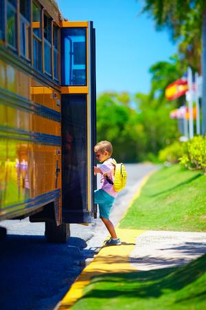 niño, cabrito que consigue en el autobús escolar, listo para ir a la escuela Foto de archivo