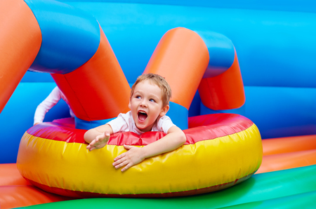 daycare: happy excited boy having fun on inflatable attraction playground Stock Photo