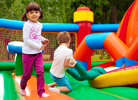excited kids having fun on inflatable attraction playground 版權商用圖片