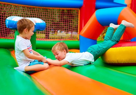 kids activities: excited kids having fun on inflatable attraction playground Stock Photo